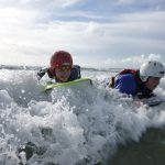 Two school students learn through adventure as they ride a wave on their body boards to a beach on anglesey