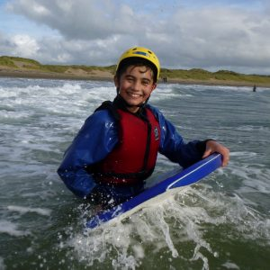 A school student on an outdoor adventure course smiles as he walks his body board back out to sea.