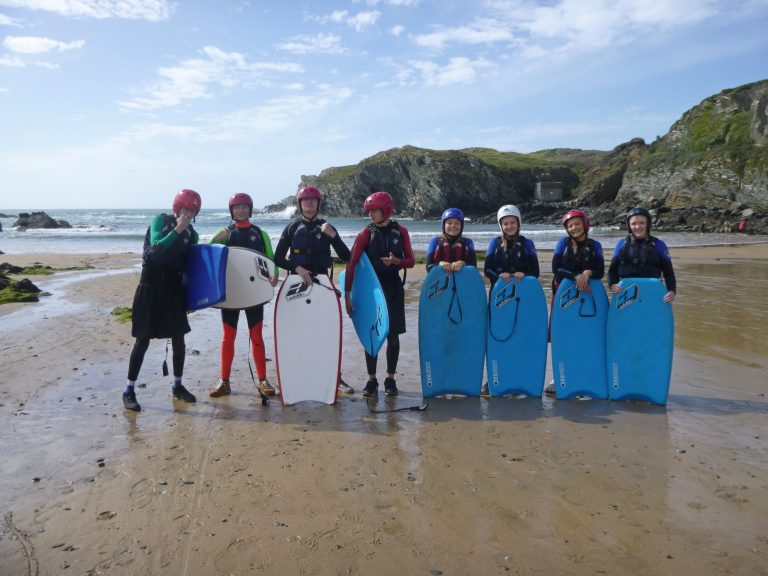 A school group take a team photo after going body boarding on anglesey