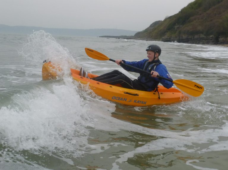 A school student paddles through a wave on a open top kayak.