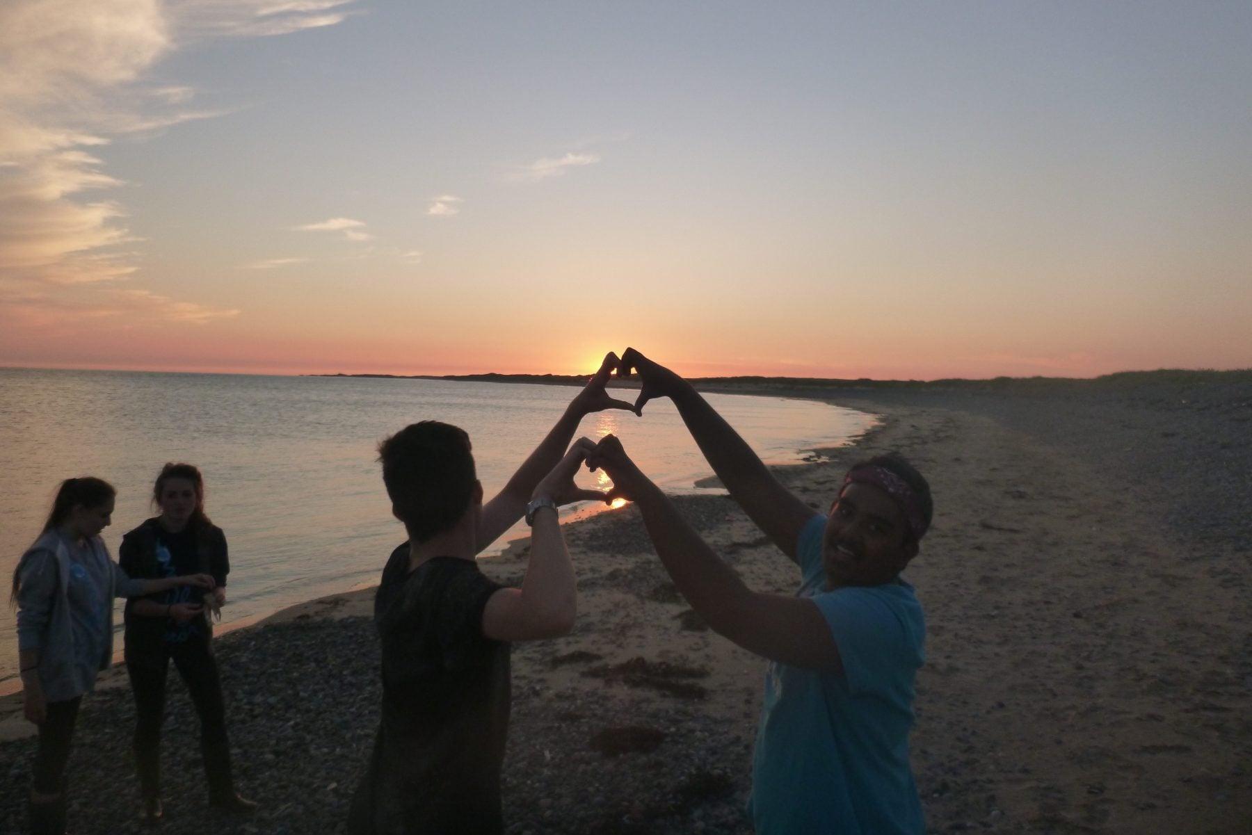 Sunset beach, team building, heart symbol