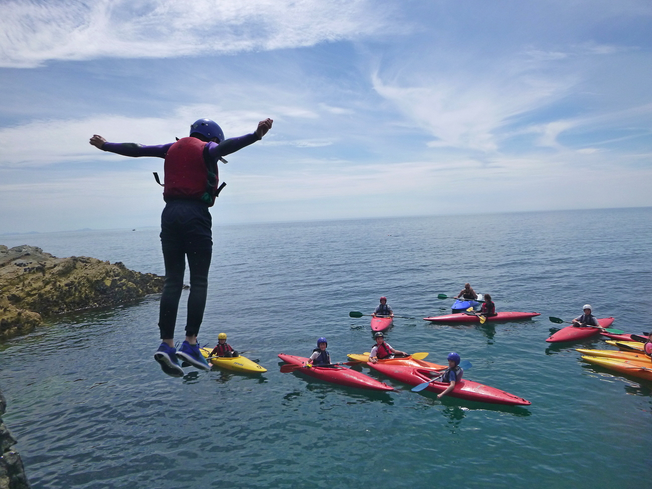 A student enjoying the thrill of Jumping into the sea whilst coasteering, a group of students watch whilst they pass on a sea kayak journey.