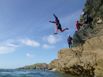 A student shows full commitment and jumps from the sea cliff into the deep sea water, whilst on a coasteering journey.