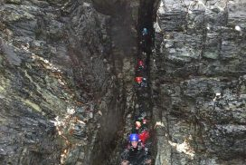 Group swimming through a tight narrow zawn whilst coasteering on Anglesey, North Wales.