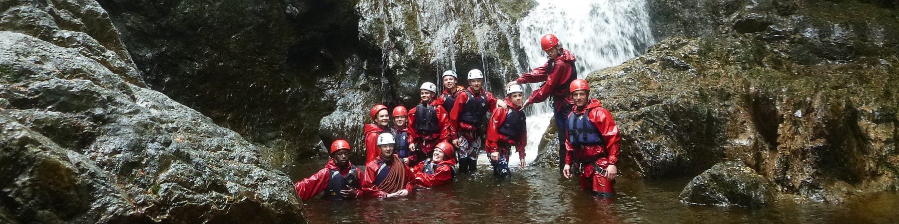 Group below waterfall in river, gorge scramble activity Snowdonia