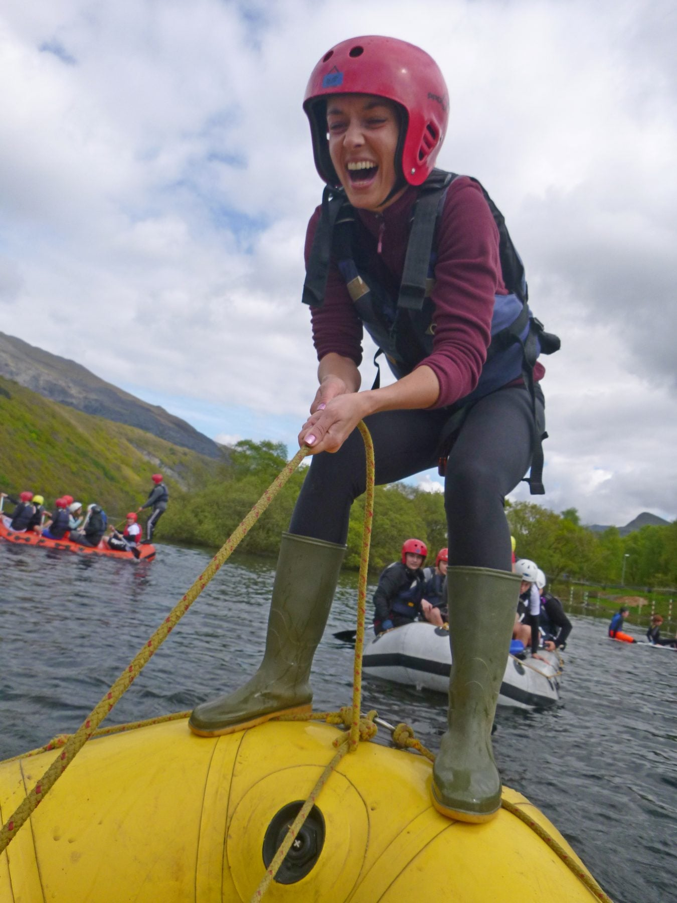 Balancing on yellow raft, secondary school pupil laughing, canoe floating on Padarn lake.