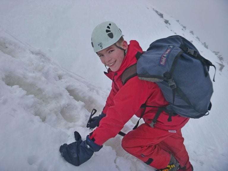 A child smiling at the camera whilst on hands and knees going up a snowy hill