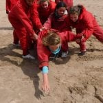 Group secondary pupils working together on beach for team building, reaching a stone part of a game