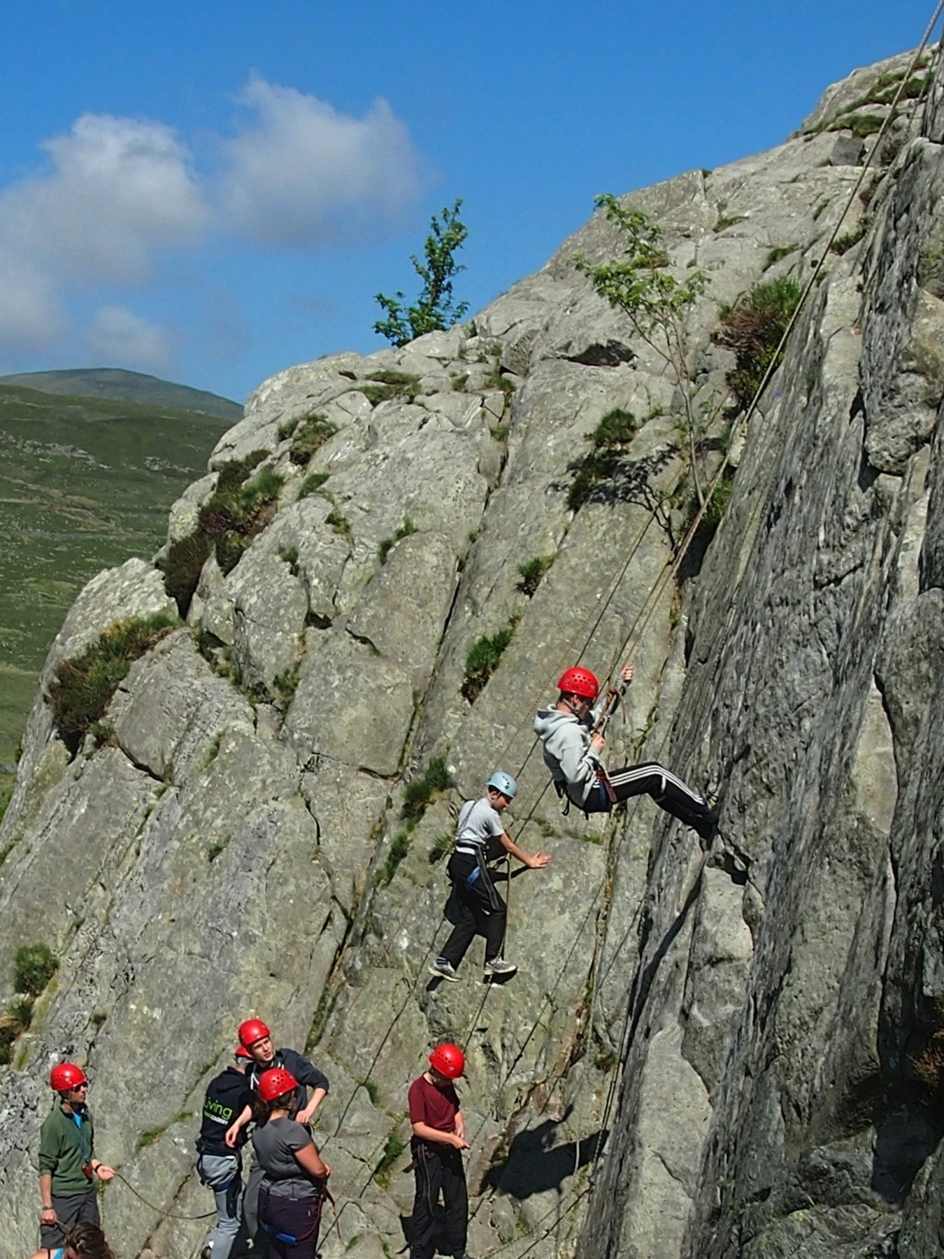 Group abseiling & climbing on single pitch cliff, Ogwen Valley, Wales