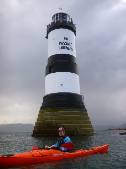 Orange sea kayak beneath black & white light house with Secondary school, Anglesey