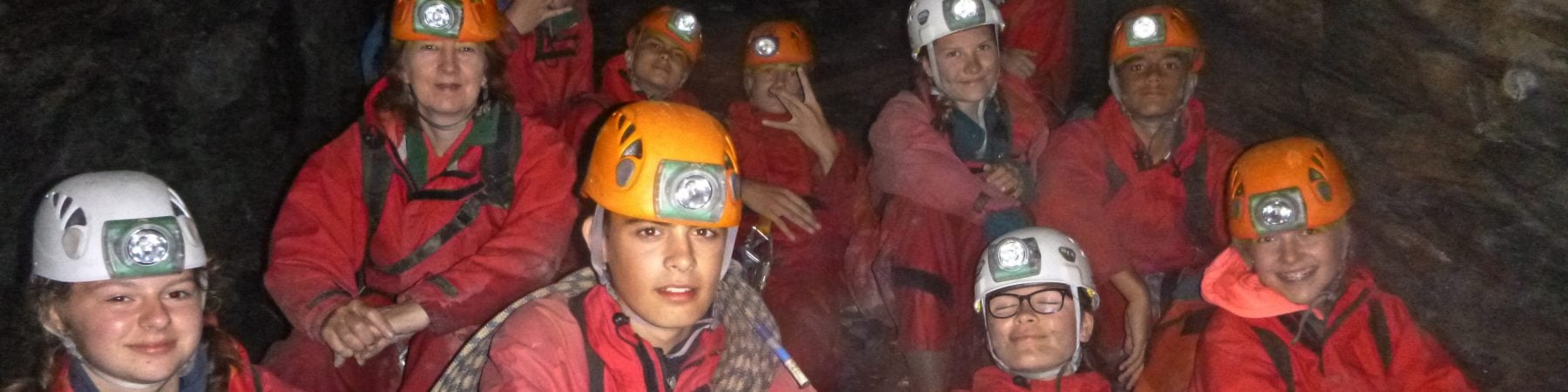 Group underground with helmets & lamps, smiling in mine while caving Snowdonia
