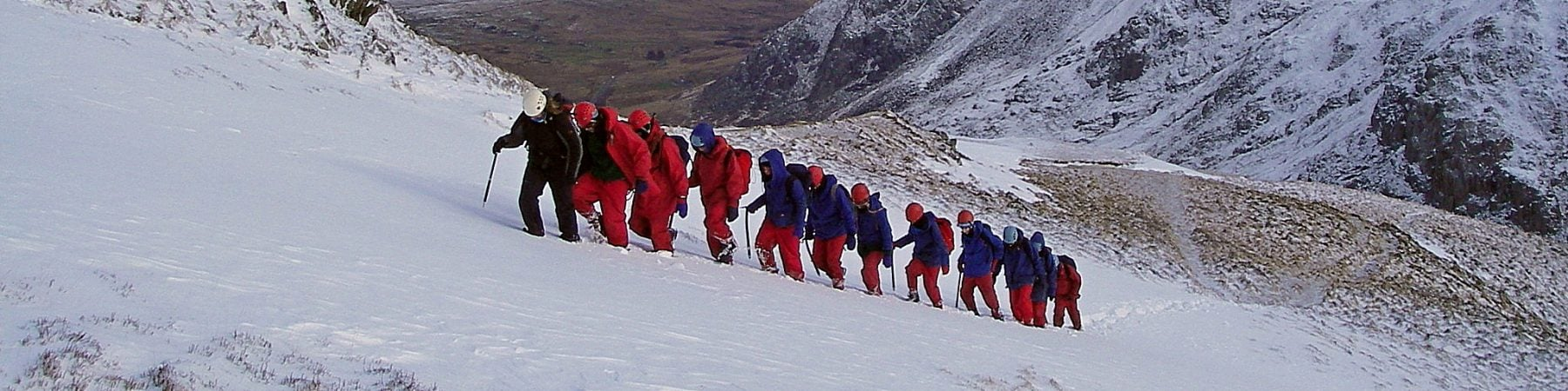 A group walking one behind another up a snowy mountain in red and blue waterproofs