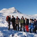 A group of adults winter mountaineering on a sunny day with the mountains in the background