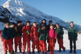 A school group posing for a picture in the snow with Crib Goch in the background