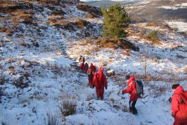 A school group walking down a path all wearing red waterproofs on a sunny winter day.
