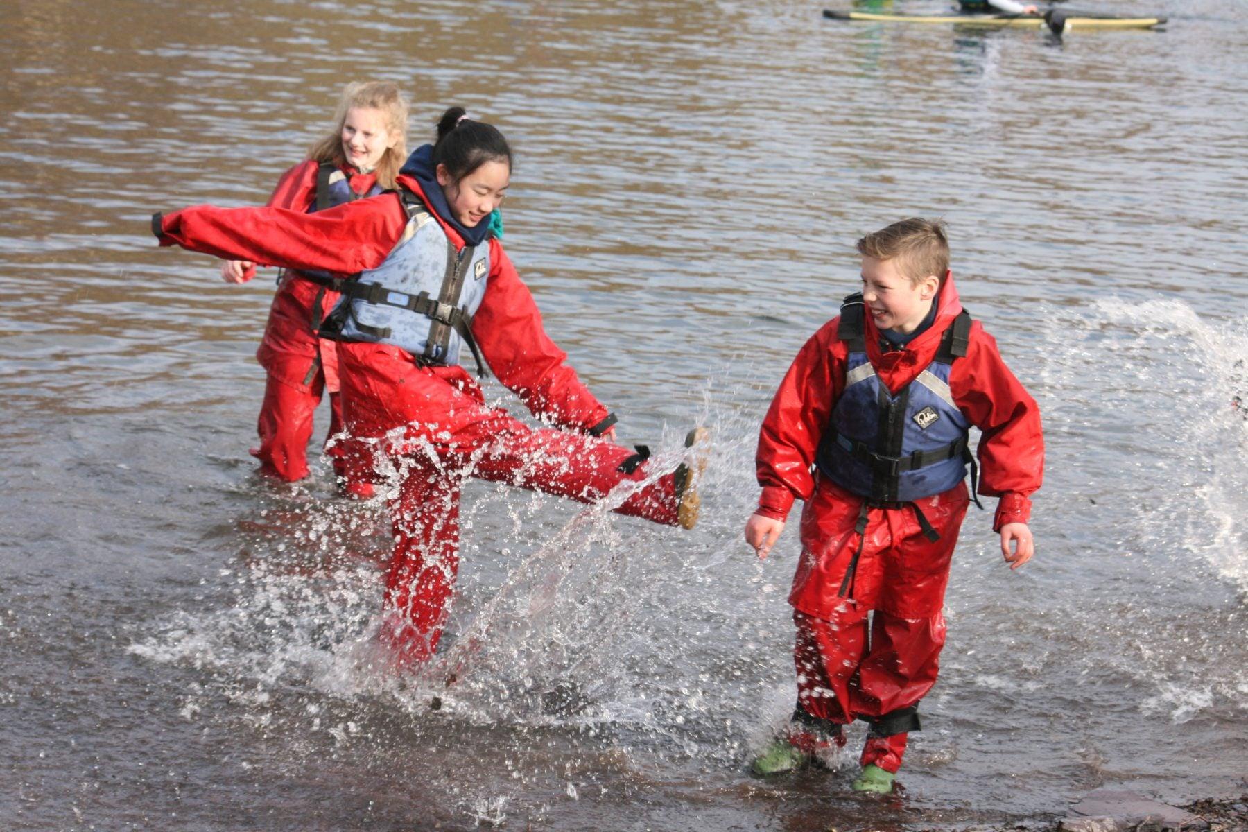 primary school pupils kicking water on outdoor activity