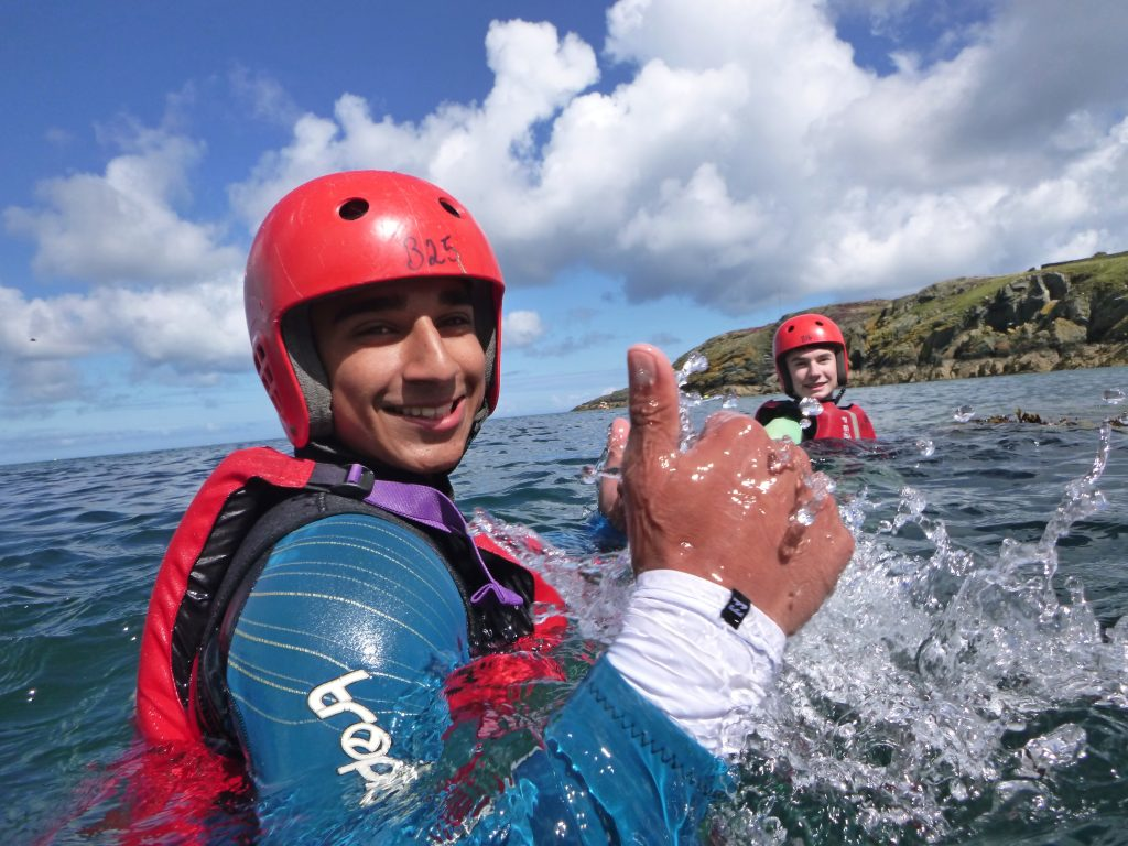 Swimming outdoors while coasteering around sea cliffs on Anglesey