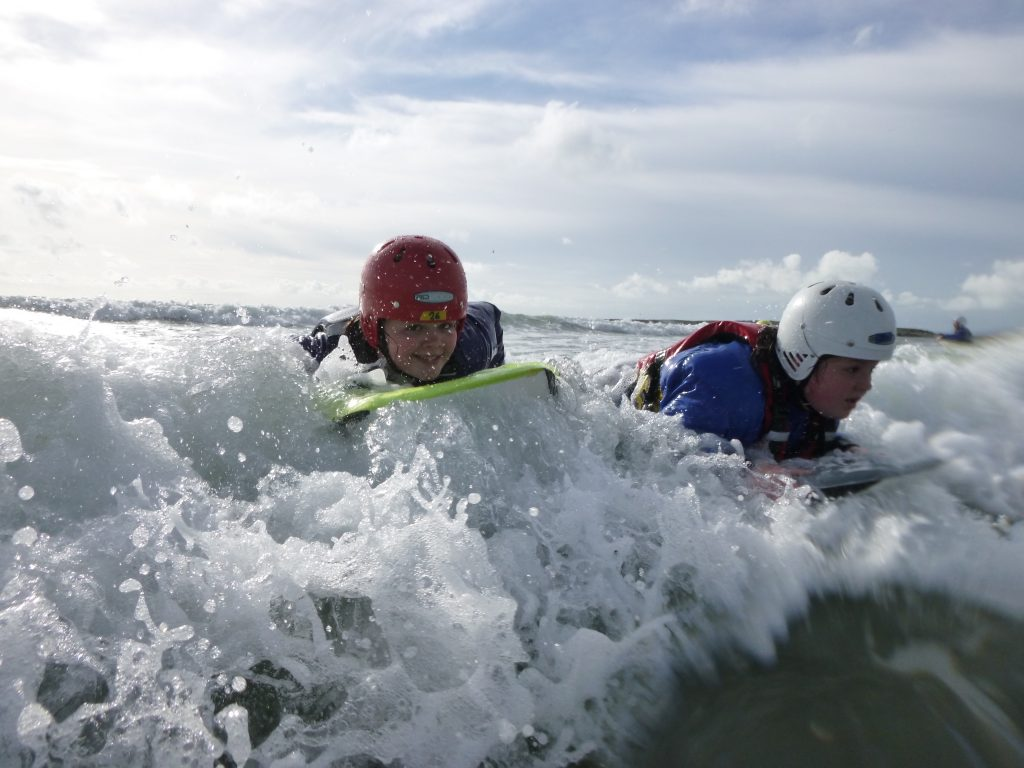 Outdoor education course body boarding in surf