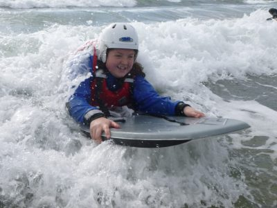 A school student rides a wave towards the beach with a smile on her face.