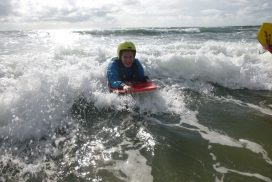 A school student on an outdoor adventure course rides a wave to the shore on her body board smiling.