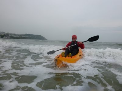 A school student surfs a wave on a open top kayak.