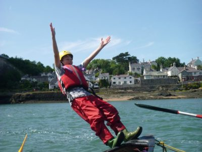 Jumping from canoe on Outdoor activity course in Menai Straits