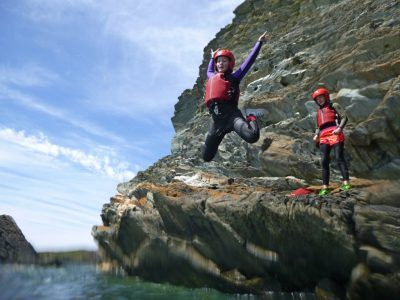 Coasteering jump into sea while outdoors in Wales
